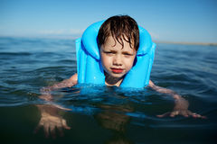 Boy in the life-vest. No smiling boy in the life-vest in the water stock photos