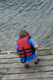 Boy in life vest. 4,5 year old in life vest on the river royalty free stock image