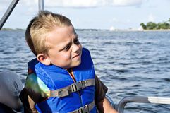 Boy in Life Vest Boating. Boy riding in a boat on the water wearing a life vest Royalty Free Stock Photo