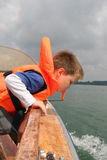 Boy in life vest leaning over boat railing. Young caucasian white boy in life vest blowing a whistle while leaning over the boat railing and looking out for royalty free stock photography