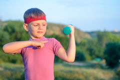 Boy Lifting Dumbbell and Pointing his Arm Muscles. Handsome Young Boy with Red Headband Lifting Dumbbell and Pointing his Arm Muscles Against Blurry Nature Royalty Free Stock Photo