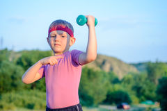 Boy Lifting Dumbbell and Pointing his Arm Muscles. Handsome Young Boy with Red Headband Lifting Dumbbell and Pointing his Arm Muscles Against Blurry Nature Stock Image