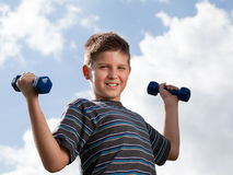 Boy lifting dumbbells outdoors Royalty Free Stock Photo