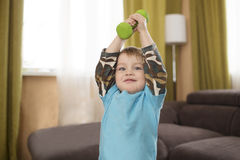 The boy lifts a dumbbell Stock Photo