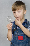 Boy and light bulb Stock Photos