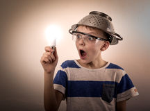 Boy with a lighted bulb in the hand Stock Photography