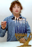 Boy lighting Menorah Stock Photography