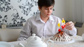 Boy lights candles on the cake stock video footage