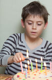 A boy lights candles on cake Royalty Free Stock Images