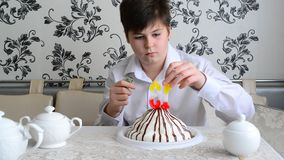 Boy lights candles on the cake with a lighter stock video