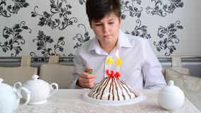 Boy lights candles on the cake with a lighter stock video footage