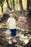 Boy with lilac and bird cage on a pond Stock Image
