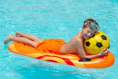 Boy on lilo in pool. Happy young boy with football relaxing on lilo in swimming pool Royalty Free Stock Images