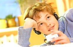 Boy listen to music. In warm sunny bedroom Stock Photos