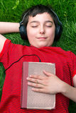 Boy listening audio book. Boy is lying on a grass and he is listening audio book Royalty Free Stock Images