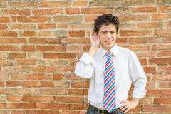 Boy listening in front of a wall stock photo