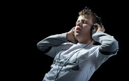 Boy listening music on black Stock Photos