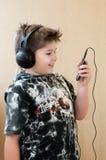 Boy listening  music with headphones Stock Photos