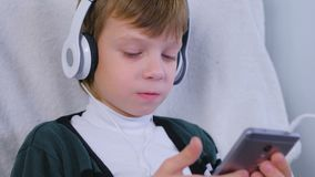 Boy is listening music in headphones in smartphone and singing sitting in armchair at home. Boy is listening music in headphones in smartphone and singing stock footage