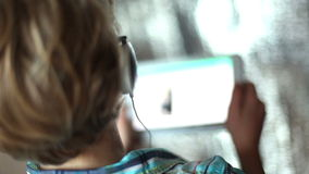 Boy listening music through headphones using a tablet PC stock video footage