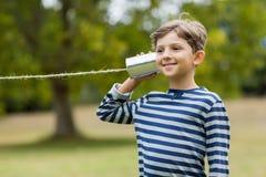 Boy listening through tin can phone. Cute boy listening through tin can phone in park Stock Photo