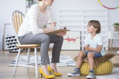 Boy listening to child therapist. Close-up of restless boy listening to a child therapist in the classroom royalty free stock photo