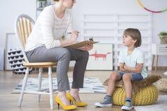 Boy listening to child therapist. Close-up of restless boy listening to a child therapist in the classroom stock photos