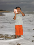 Boy listening to the conch. Asian boy listening to the conch in the beach Stock Images