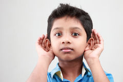 Boy listening to a low voice Stock Photos