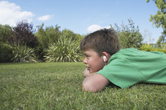 Boy Listening To MP3 Player On Grass  Royalty Free Stock Photos