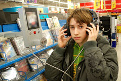 Boy listening to the music. Teenager listening to the music in a store Royalty Free Stock Image