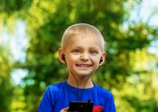 Boy listening to music. Cute smiling little boy with cell phone and earphones listening to music in summer park Stock Image
