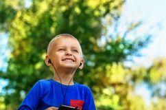 Boy listening to music. Cute smiling little boy with cell phone and earphones listening to music in summer park Royalty Free Stock Photo
