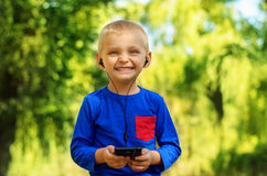 Boy listening to music. Cute smiling little boy with cell phone and earphones listening to music in summer park Royalty Free Stock Photos
