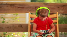 Boy listening to music on green headphones stock footage