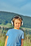 Boy listening to music on headphones in nature Stock Image
