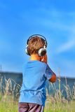 Boy listening to music on headphones in nature Royalty Free Stock Images