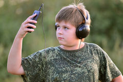 Boy listening to music on headphones with smartphone Stock Image