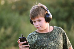Boy listening to music on headphones with smartphone Stock Images
