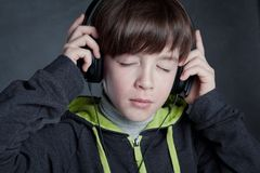 Boy listening to music on headphones Stock Images