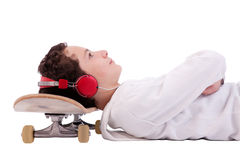 Boy listening to music with his head on skateboard Royalty Free Stock Images