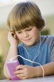 Boy Listening to Music on MP3 Player Stock Photos