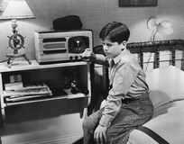 Boy listening to radio in bedroom. (All persons depicted are no longer living and no estate exists. Supplier grants that there will be no model release issues Royalty Free Stock Images
