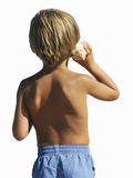 Boy listening to sea shell, rear view, cut out Royalty Free Stock Photos