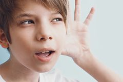 Boy listens attentively, raising his hand to his ear. Portrait of kid. Emotion concept stock photography