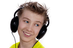 The boy listens to music. The cheerful boy in headphones Stock Images