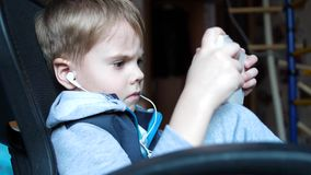 The boy listens to music through headphones. In the children`s room the child enjoys music stock video footage