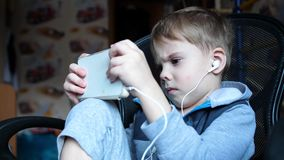 The boy listens to music through headphones. In the children`s room the child enjoys music stock footage