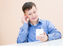The boy listens to music. At the table Royalty Free Stock Photo