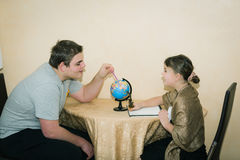 boy and little beautiful girl sitting and having fun with exploring and learning the world globe Stock Images